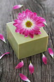 Bar of natural green soap with flower — Stock Photo