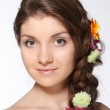 Beauty young brunette girl with flowers — Stock Photo