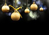 Gold Christmas balls on a multi coloured sparkling background — Stock Photo