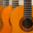 Row of classical acoustic guitars in musical store. Close-up vie - Stock Photo