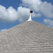 Gray tiled roof top under blue sky - Stock Photo