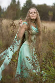 Romantic long-haired girl in green dress — Stock Photo