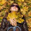 The beautiful girl with autumn leaves — Stockfoto