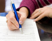 Female hands with a pencil write on a paper — Stock Photo