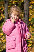 The little girl talks on a cellular telephone — Stock Photo