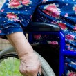 Hand of the old woman on an invalid armchair — Stock Photo