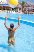 Het meisje speelt een bal in zwembad — Stockfoto