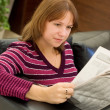The girl reads the newspaper in an armchair - Stock Photo