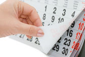 The hand overturns calendar sheet isolated on white background — Stock Photo