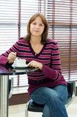 La ragazza beve caffè dietro un tavolo in caffetteria — Foto Stock