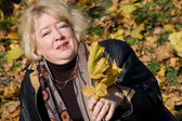 La belle femme avec des feuilles d'automne — Photo