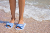 Feet in flip flops at the sea — Stock Photo