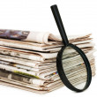 Magnify glass over a stack of newspaper — Stock Photo #4454393