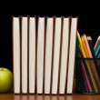 Stack of books and apple on a wooden table — Stock Photo