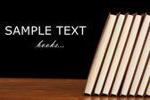 Knihy na dřevěný stůl na černém pozadí — Stock fotografie
