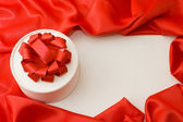 Box with a gift on a red fabric — Stock Photo