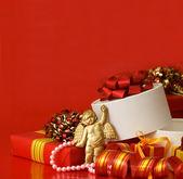 Boîte avec un cadeau sur fond rouge — Photo