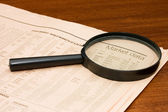 Magnify glass and the newspaper on a wooden table — Stock Photo