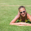 The young girl lays on a grass — Stock Photo