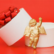 Box with a gift on a red background - Stock Photo