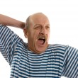 Elderly  man in a stripped vest yawns - Stock Photo