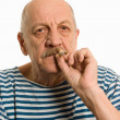Elderly man in a stripped vest smokes - Stock Photo