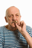 Elderly man in a stripped vest smokes — Stock Photo