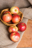 Apples on a sacking on a wooden table — Stock Photo