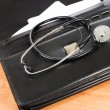 Stock Photo: Black portfolio and phonendoscope on a table