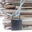 Stock Photo: Pile of newspapers with chains, on white