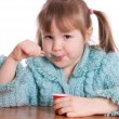 Stock Photo: The little girl eats yoghurt