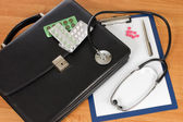 черный портфель и фонендоскоп на столе — Стоковое фото