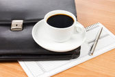Black portfolio and coffee on a table — Stock Photo