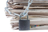 Pile of newspapers with chains, on white — Stock Photo