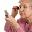 The elderly woman does a make-up — Stock Photo