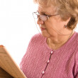 The elderly woman reads the newspaper — Stock Photo #4976124