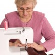 The elderly woman sews on the sewing machine — Stock Photo #4976133