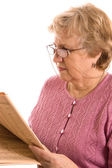 The elderly woman reads the newspaper — Stock Photo