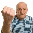 The elderly man threatens with a fist - Stock Photo
