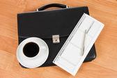 Black portfolio and coffee on a table — Stock Photo