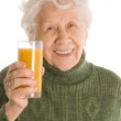 The elderly woman with a juice glass — Stock Photo