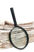 Magnify glass over a stack of newspaper — Stock Photo