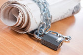 Newspapers with chains On a wooden table — Stock Photo