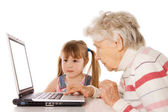 The grandmother with the grand daughter at the computer — Stock Photo