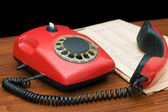 Red phone on a wooden table — Stockfoto