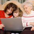 Family on a sofa with the computer — Stock Photo