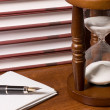 Stock Photo: Hourglasses and book on a wooden table
