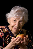 Apple in a hand of the old woman on the black — Стоковое фото