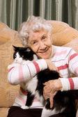 La grand-mère avec un chat sur un canapé — Photo