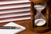 Relojes de arena y libro sobre una mesa de madera — Foto de Stock